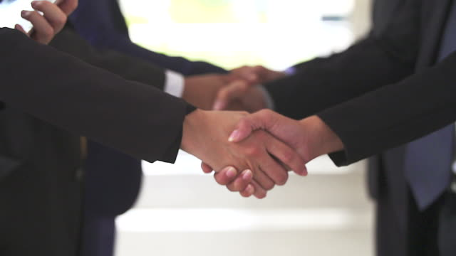 business handshake of two men demonstrating their agreement to sign agreement or contract between their firms / companies / enterprises. - support stock videos & royalty-free footage