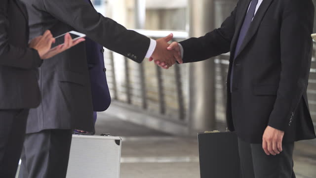 Business handshake of two men demonstrating their agreement to sign agreement or contract between their firms / companies / enterprises.