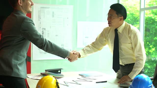 vídeos de stock, filmes e b-roll de aperto de mão de negócios de dois homens, demonstrando o seu acordo para assinar o acordo ou contrato entre suas empresas / empresas / empresas. - conformidade