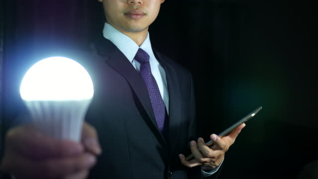 Business idea and vision, businessman holding shining light bulb, concept of new ideas, innovation, invention and creativity.