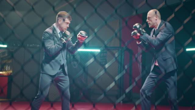 vidéos et rushes de les affaires sont un jeu difficile. hommes d'affaires fâchés dans l'anneau de boîte - arts martiaux