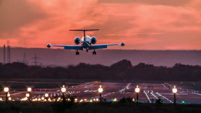 business jet landing on airport runway at dusk - aeroplane stock videos & royalty-free footage