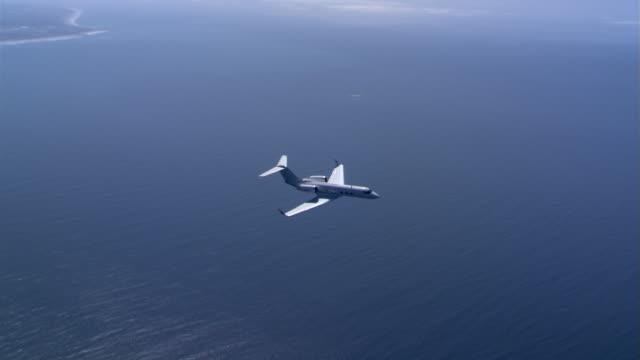 vidéos et rushes de business jet over nearshore ocean - avion privé d'entreprise