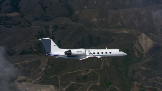 business jet over rugged terrain - artbeats stock videos & royalty-free footage