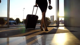 Business lady going to the airport with her luggage. Young woman in heels entering walking through glass doors to the terminal and roll suitcase on wheels. Trip or vacation travel concept. Slow motion Close up