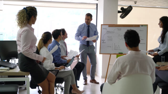 stockvideo's en b-roll-footage met bedrijfsleider in een meeting die zijn team aanpakt tijdens een training en wijzend op whiteboard - workshop