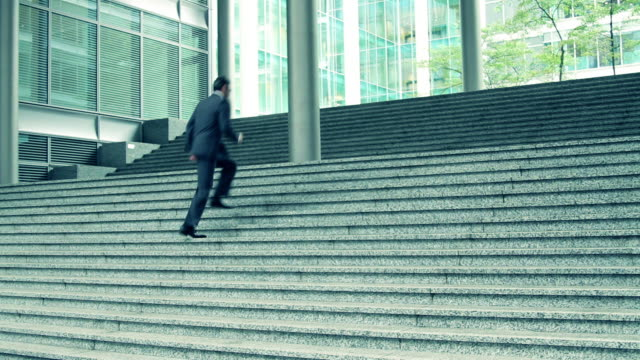 Business male running up office entrance steps