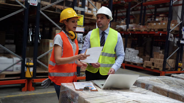 business man and female supervisor of a distribution warehouse discussing something while looking at laptop and paperwork - world trade organisation stock videos & royalty-free footage