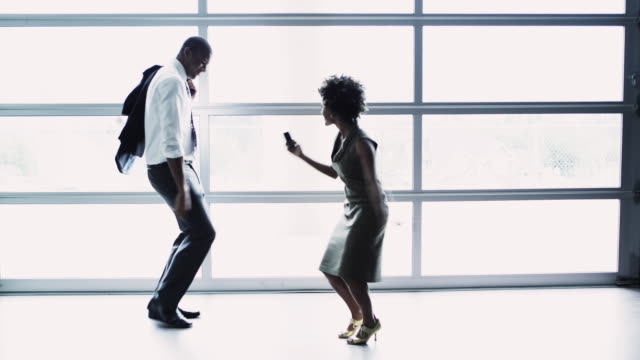 WS R/F Business man and woman dancing in front of window, Squamish, British Columbia, Canada