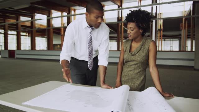 MS DS TU Business man and woman discussing blueprint, Squamish, British Columbia, Canada