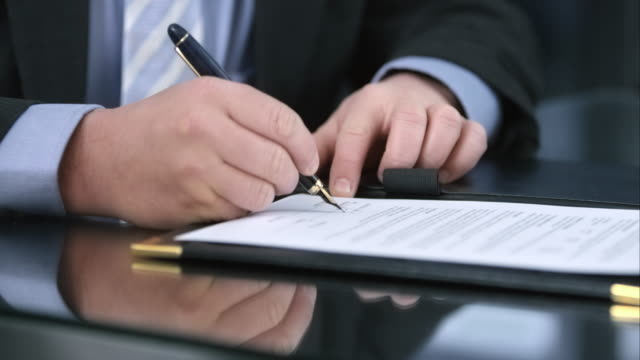 slo mo business man and woman signing the contract - signing stock videos & royalty-free footage