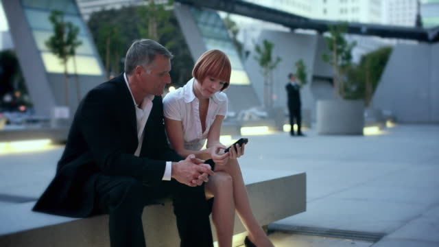 MS Business man and woman sitting in office park, woman looking at man's phone, Los Angeles, California, USA