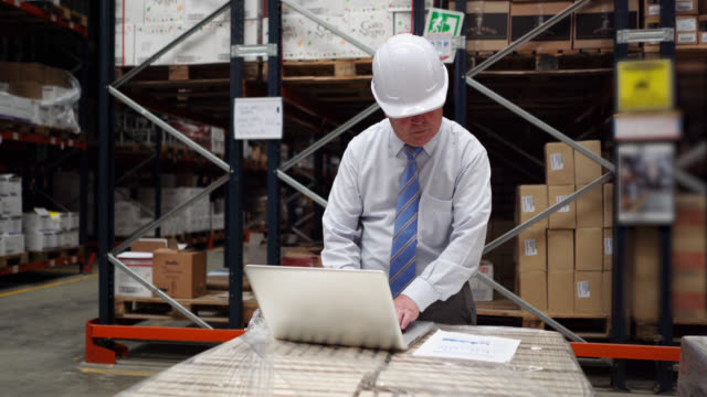 business man at a distribution warehouse typing something on laptop very focused - world trade organisation stock videos & royalty-free footage
