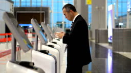 Business man at the airport check in ticket at kiosk terminal