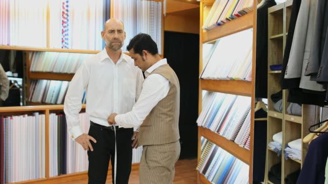 オーダーメイドのスーツをカスタム測定されているビジネスの男性 - 生地サンプル点の映像素材/bロール