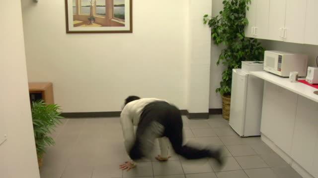 MS, Business man break dancing in snack room in office, Compton, California, USA