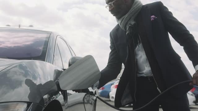 vídeos y material grabado en eventos de stock de business man charging electric car at charging station in city wearing suit - coche eléctrico coche alternativo