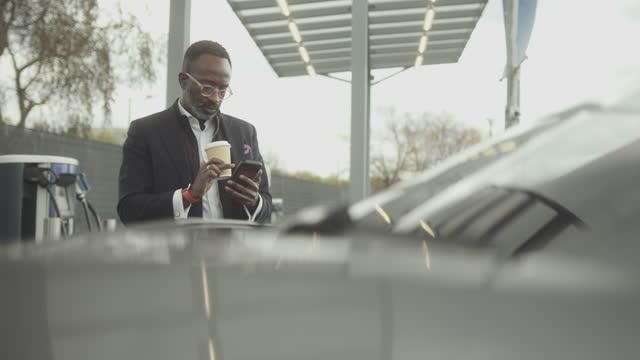 vídeos y material grabado en eventos de stock de business man charging electric car at charging station looking at smart phone and drinking coffee - coche eléctrico coche alternativo
