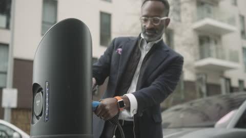 vídeos y material grabado en eventos de stock de business man charging electric car at charging station on street - coche eléctrico coche alternativo