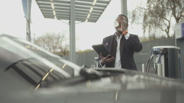 vídeos y material grabado en eventos de stock de business man charging electric car at charging station wearing suit and working on digital tablet - coche eléctrico coche alternativo