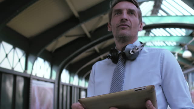 business man checking his tablet for connections - railway station platform stock videos & royalty-free footage