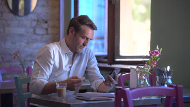 Business man checking smartphone in a café