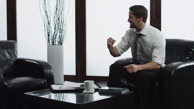 vídeos de stock, filmes e b-roll de ms business man cheering while using digital tablet in lobby / orem, utah, usa - orem