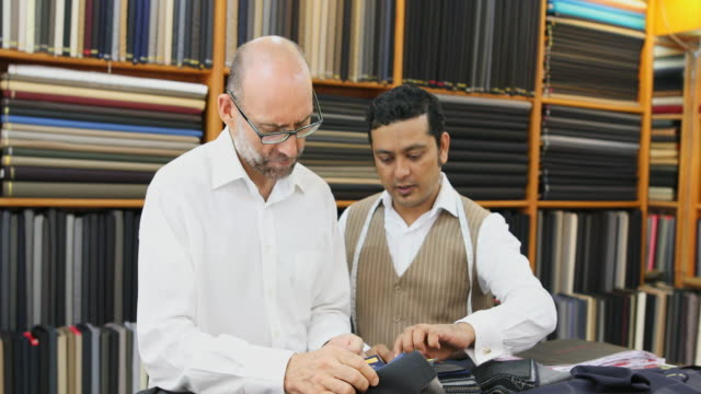 Business Man Choosing Fabric For a Custom Tailored Suit