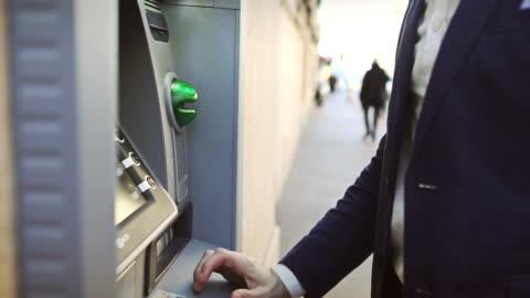 vidéos et rushes de homme d'affaires de retrait de la carte de crédit de la banque - enlever