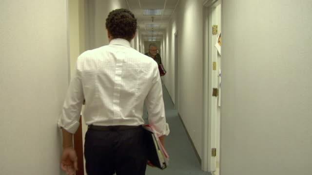 vidéos et rushes de ms, business man dropping folders bumping into colleague walking through office hallway, compton, california, usa - heurter