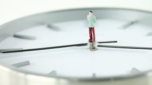 vídeos de stock e filmes b-roll de cu business man figurine standing on clock / seoul, south korea - figura masculina