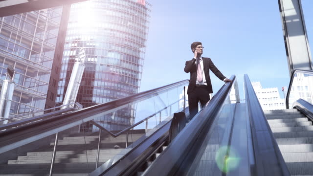 business man goes down an escalator - potsdamer platz stock videos & royalty-free footage