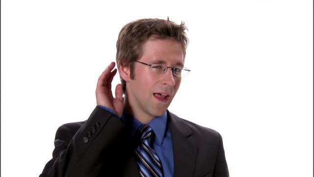 cu, business man holding hand to ear, portrait, studio shot - ascoltare video stock e b–roll