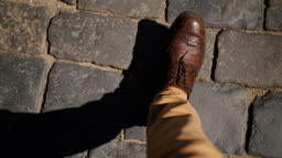 Business Man in a brown leather shoes stepping on the pavement, top view in the first person.