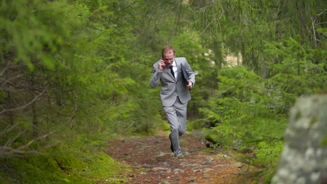 business man in a grey suit running down a path in a green forest while speaking on smartphone - only mid adult men stock videos & royalty-free footage