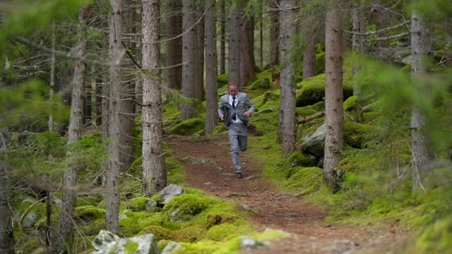 business man in a grey suit running down a path in a green forest - offbeat stock videos & royalty-free footage