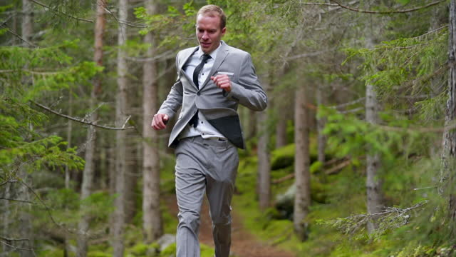 business man in a grey suit running down a path in a green forest - one mid adult man only stock videos & royalty-free footage