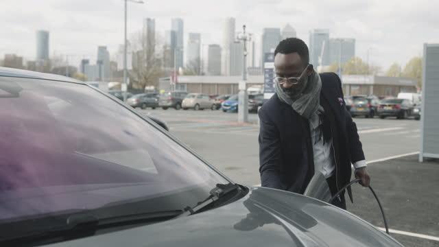 vídeos y material grabado en eventos de stock de business man in city charging electric car at charging station with skyline - coche eléctrico coche alternativo