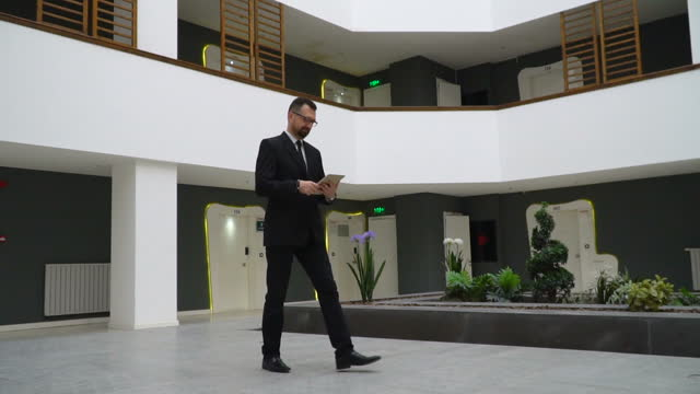 business man is checking his daily workflow in the lobby of modern office - lobby stock videos & royalty-free footage