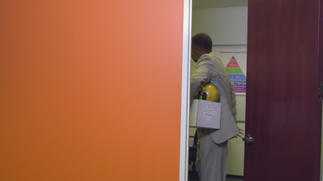 MS Business man leaving office, carrying box, Austin, Texas, USA