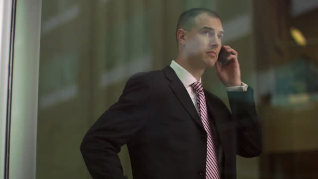 vídeos y material grabado en eventos de stock de ms ds business man looking out window and talking on phone / south orange, new jersey, usa - detrás