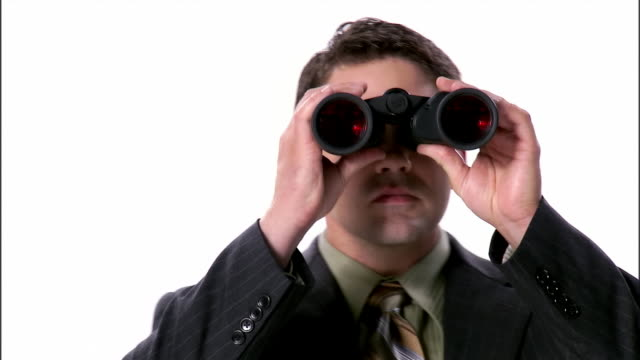 cu, business man looking through binoculars, portrait, studio shot - binoculars stock videos & royalty-free footage