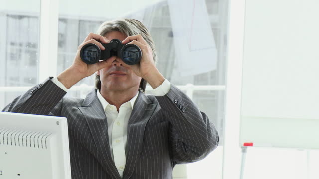 cu pan business man looking through binoculars sitting in office / cape town, western cape, south africa - canocchiale video stock e b–roll
