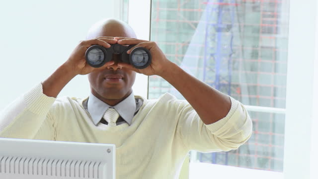 cu pan business man looking through binoculars sitting in office / cape town, western cape, south africa - office politics stock videos & royalty-free footage