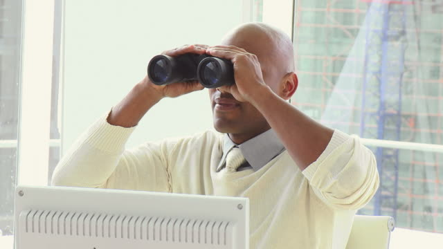 cu business man looking through binoculars sitting in office / cape town, western cape, south africa - office politics stock videos & royalty-free footage