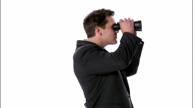 ms, business man looking through binoculars, studio shot - binoculars stock videos & royalty-free footage