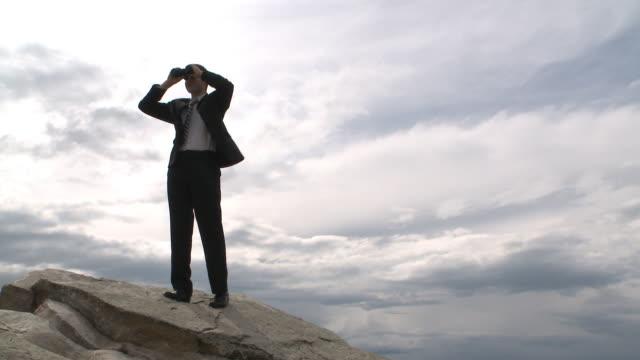 stockvideo's en b-roll-footage met business man looks to the future atop a mountain - verrekijker