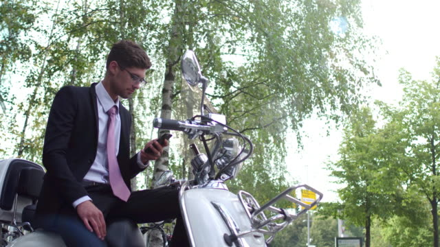 Business man on motor scooter uses his phone
