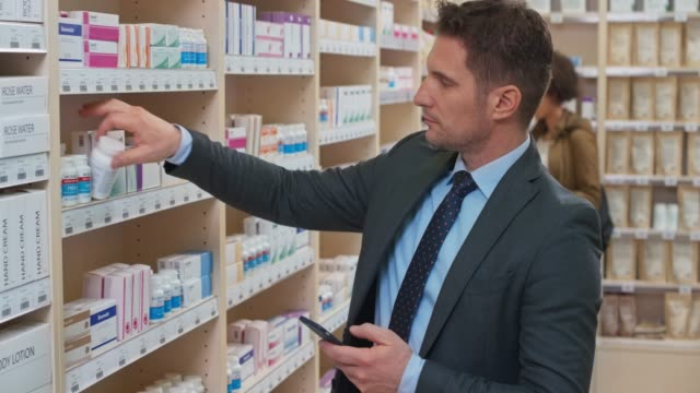 ds business man picking up a medicine bottle at the drugstore while checking his phone - pharmacy stock videos & royalty-free footage