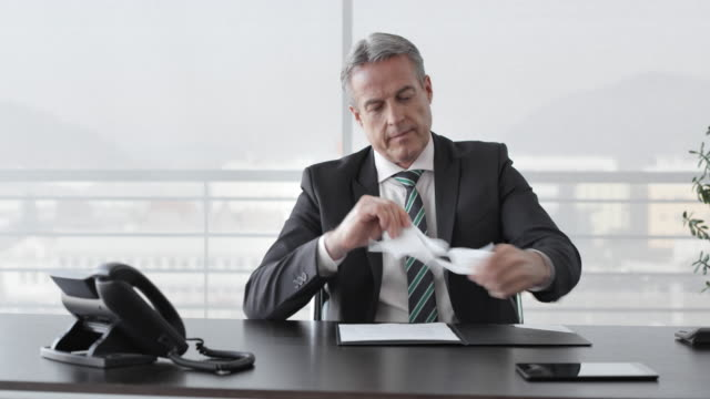 DS Business man reading and tearing up a document